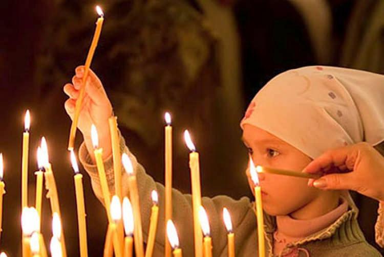 Ребенок ставит свечу